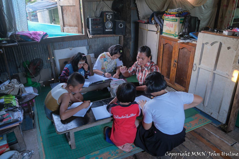 A Burmese migrant community volunteer teacher holds a class at home because migrant schools are closed; here they are learning the Burmese language.